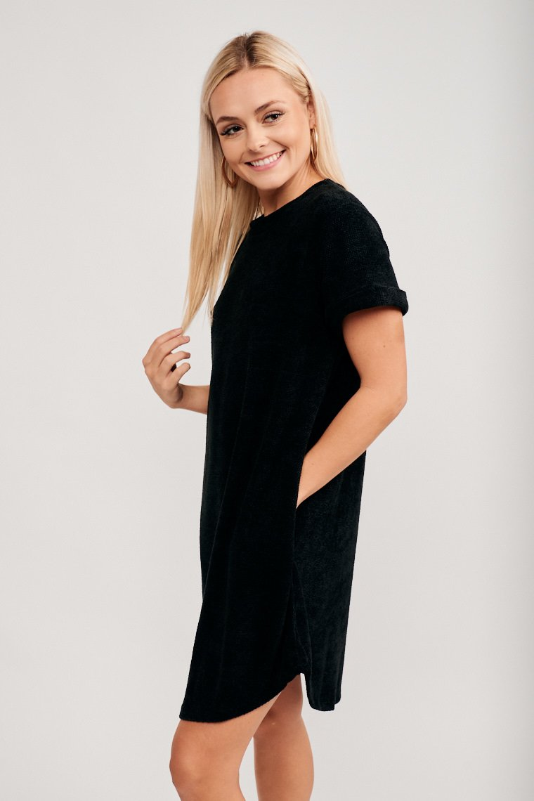 Short cuffed sleeves attach to a u-neckline and lead into a shift silhouette with pockets at the side. Pair with a contrasting fuzzy vest, hairpins, and booties.