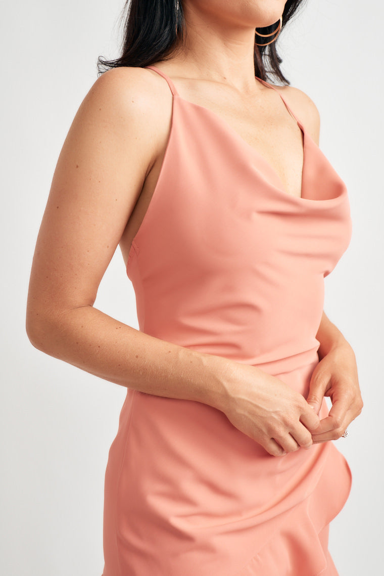 Cowl neckline supported by adjustable strap crossing on the back. The figure-skimming silhouette with cascading ruffle detail along the front with shorts under.