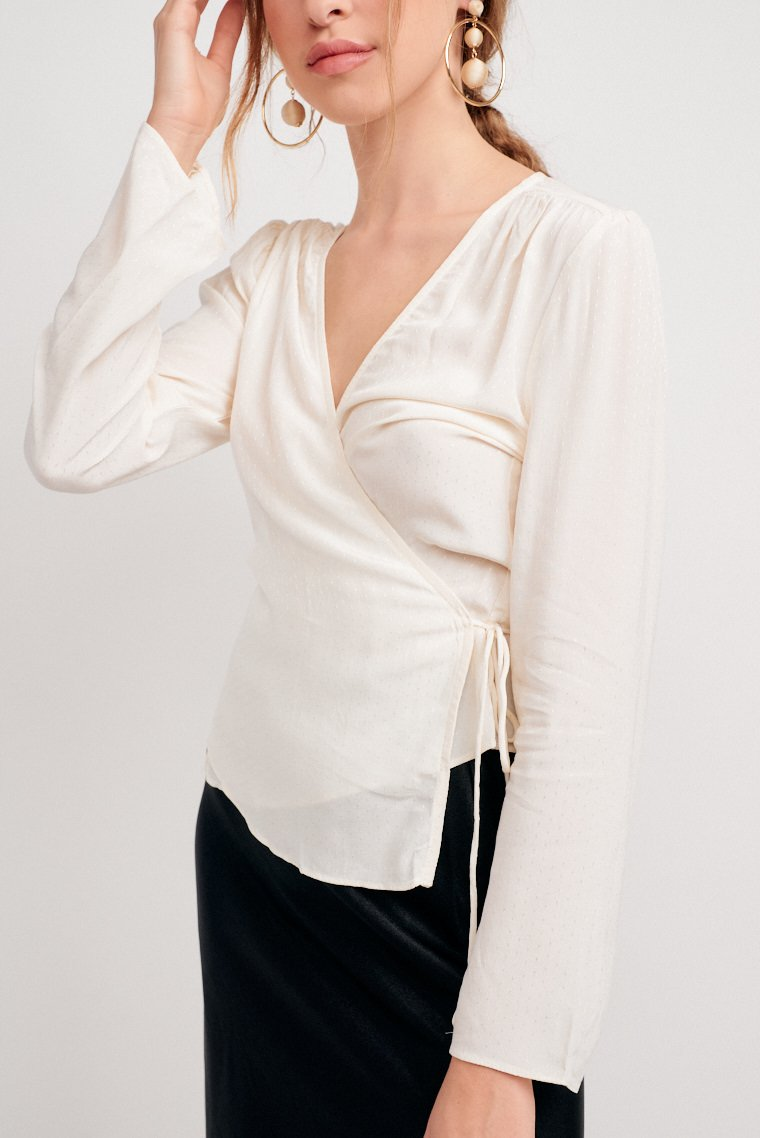 This lightweight top has small dotted flecks. Long sleeves attach to a surplice neckline and lead to a comfortable fit and wrapped bodice silhouette with a tie.