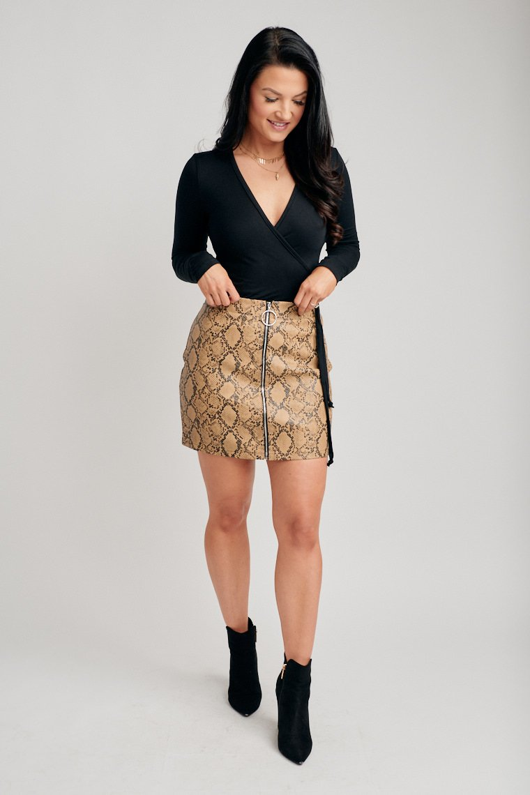 Black snake prints cover the fabric of this skirt. It has a fitted waistband that leads to a ring zipper that goes down the fitted mini pencil skirt.