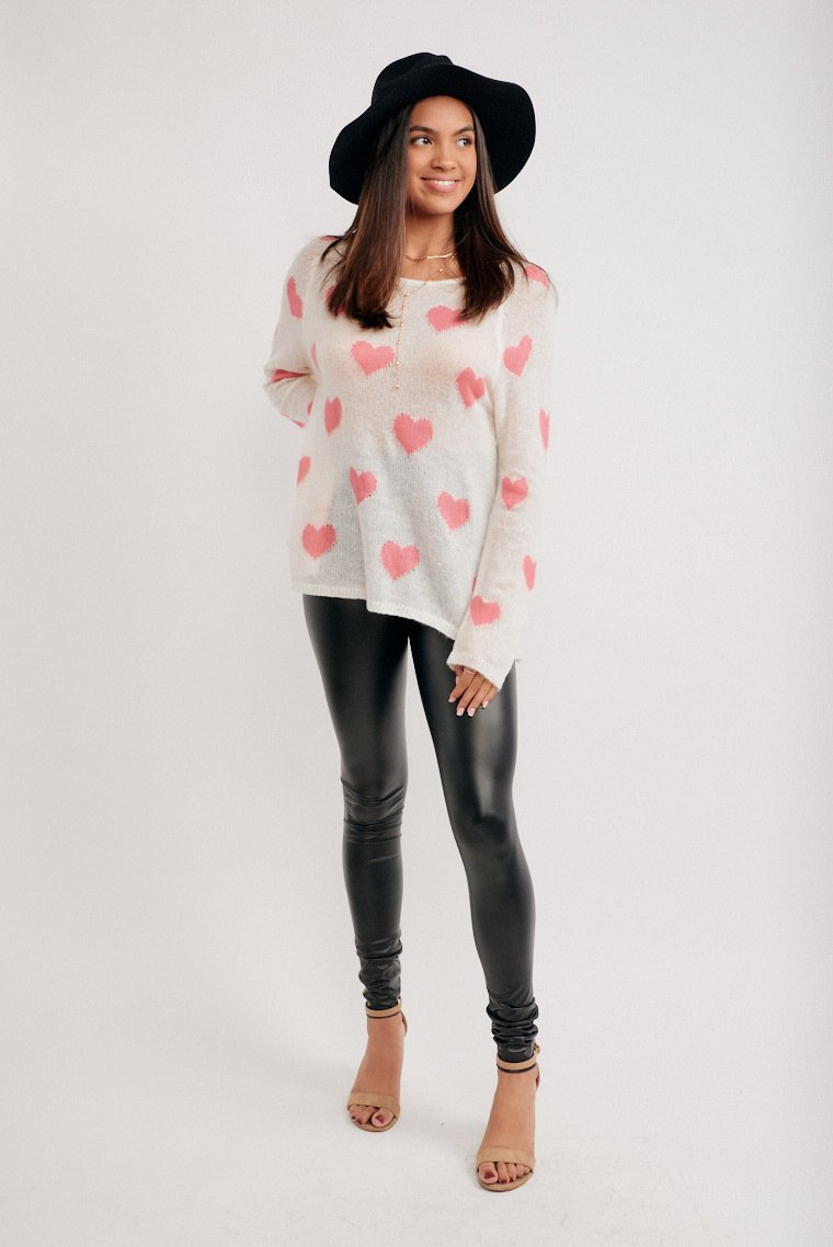 Pink starts cover this lightweight yet cozy and fuzzy sweater. It has long sleeves that attach to a u-neckline and goes into an oversized and relaxed bodice silhouette.