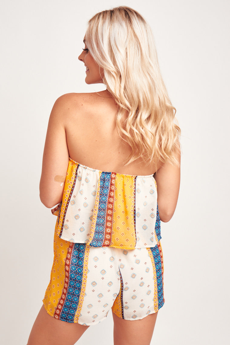 Colorful prints paint this patterned romper with a straight elastic neckline and flounced bodice atop an elastic waistband that leads into relaxed shorts with pockets.
