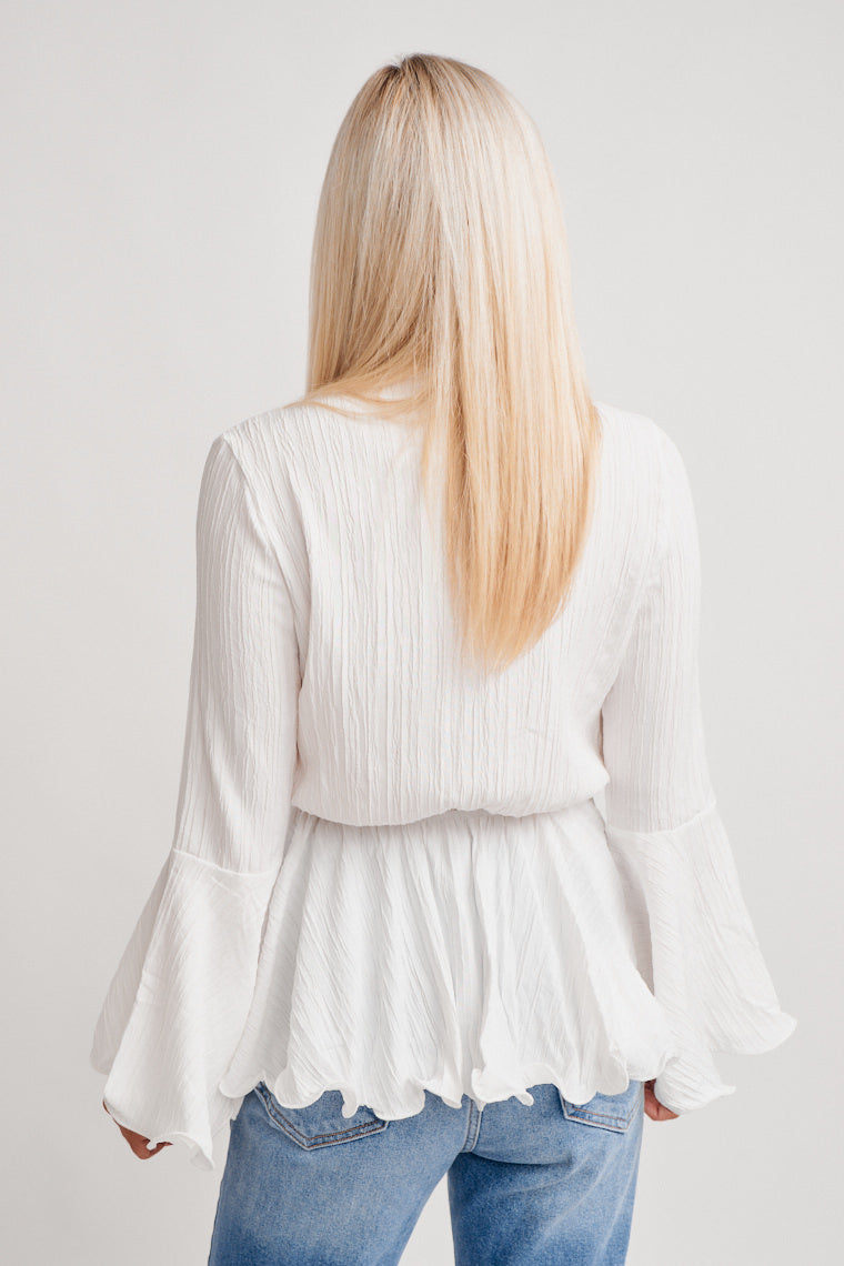 Long bell sleeves attach to a deep v-neckline and comfortable fit bodice and lead to a tie-front hem and elastic waistband that flared into a peplum-style waist.