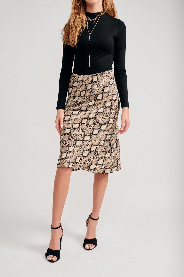 This midi skirt has black and tan snake print across this fabric. It has an elastic waistband that hugs at the waist and hips and flows down to pencil silhouette.