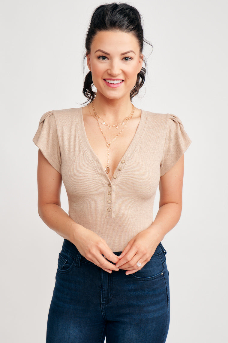 This taupe bodysuit offers a v-neckline, button down detail on ribbed fabric, and flows into puffed sleeves. This bodysuit features plastic closures in the inseam.
