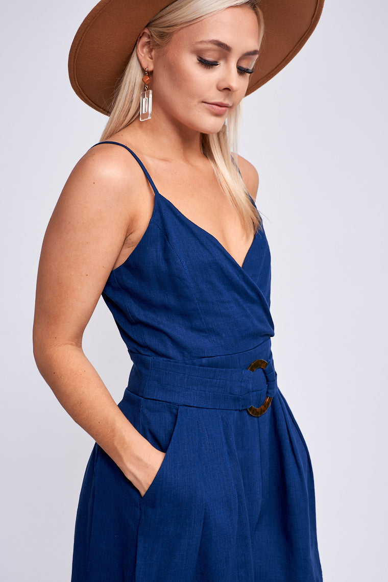 Thin adjustable straps attach to a surplice neckline bodice and meet sewn-in front belt with an acrylic o-ring detail before going into pleated and relaxed shorts.