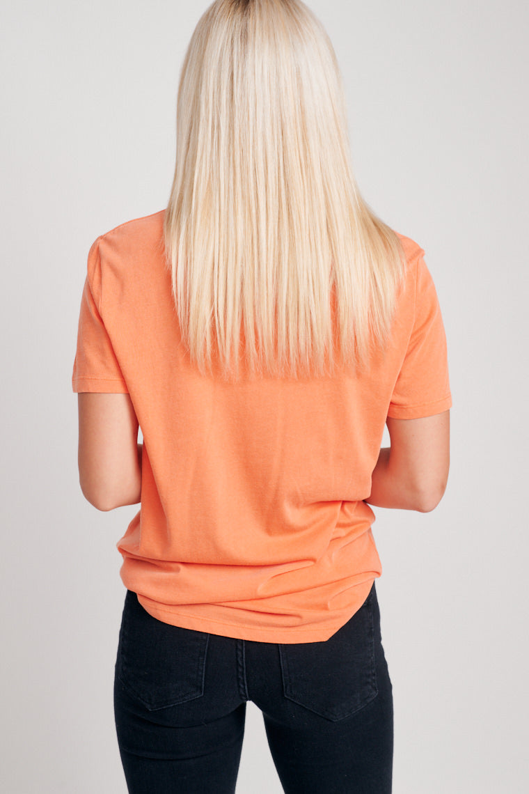 "This orange u-neckline tee with a relaxed bodice has grey script text of the words ""Trick Or Treat Yo Self."" Pair with medium wash jeans,"