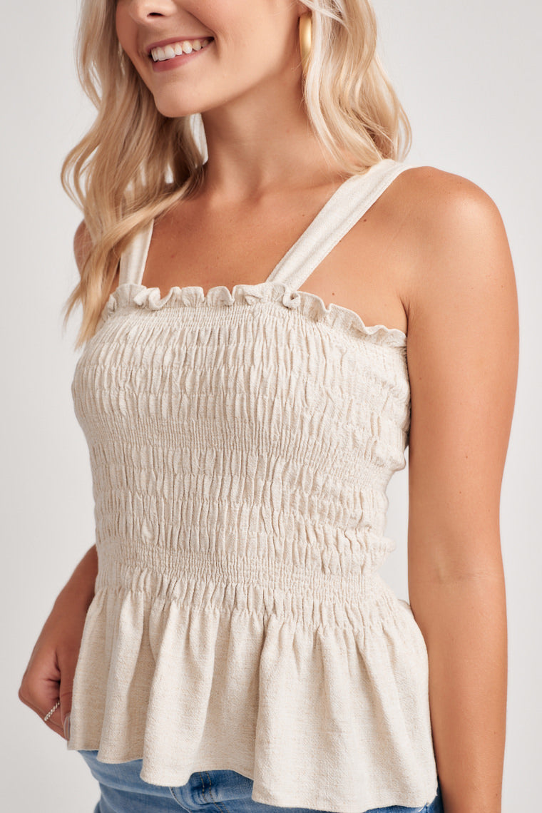 Lightweight and stretch fabric create this tank in a neutral shade. Thick straps support the ruffled neckline accompanied by a peplum hem and smocked bodice.