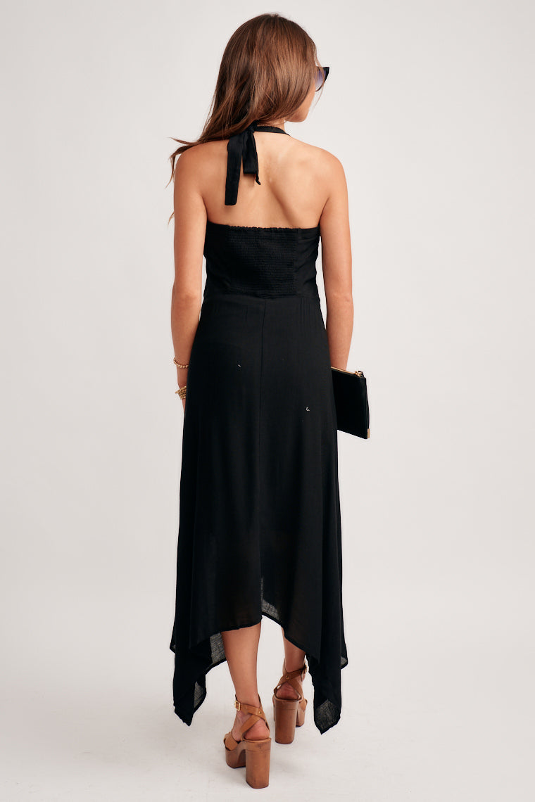 This halter dress offers a gentle sweetheart neckline, a fitted bodice with stitching across the waist that flows into a layered handkerchief skirt.