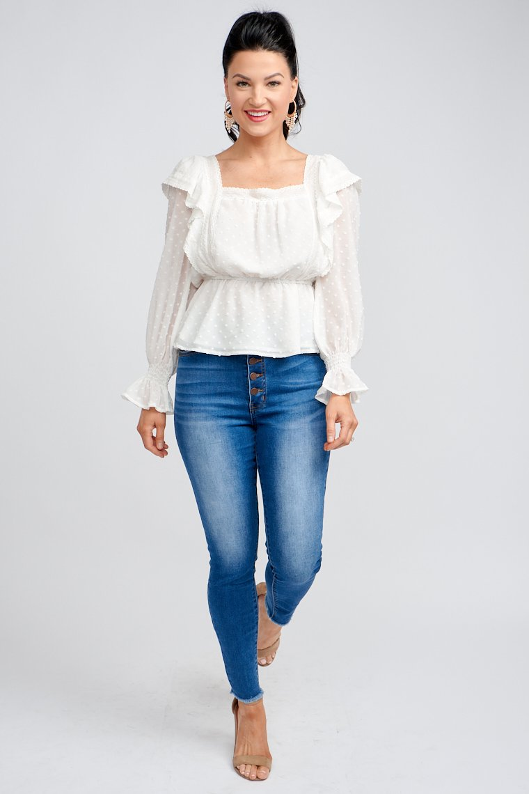 Small swiss dots, long elastic cuff and ruffled sleeves attach to a square neckline with a lace-trimmed ruffle hem that leads down a relaxed bodice silhouette.