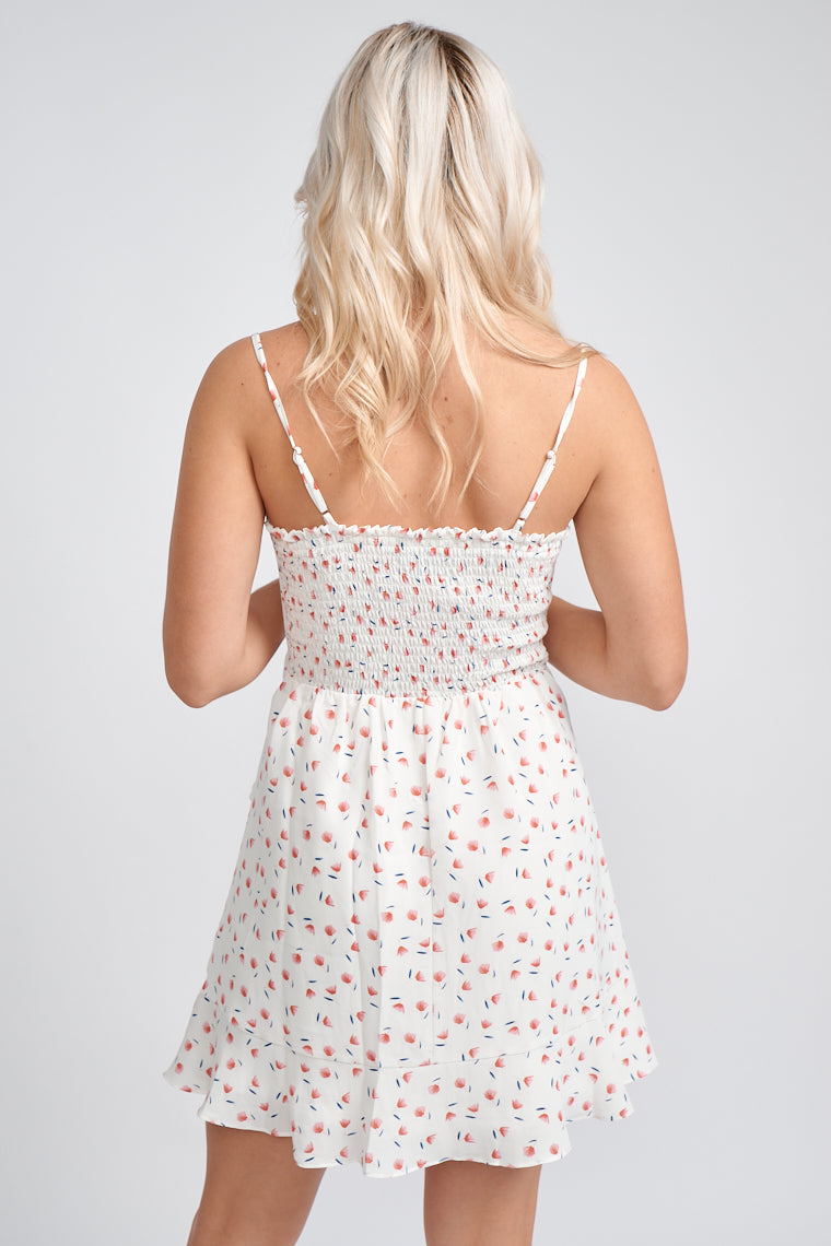 Thin adjustable straps attach to a straight neckline on a fitted and darted bodice with skirt panel that lays atop a ruffled mini skirt silhouette with a fabric tie.