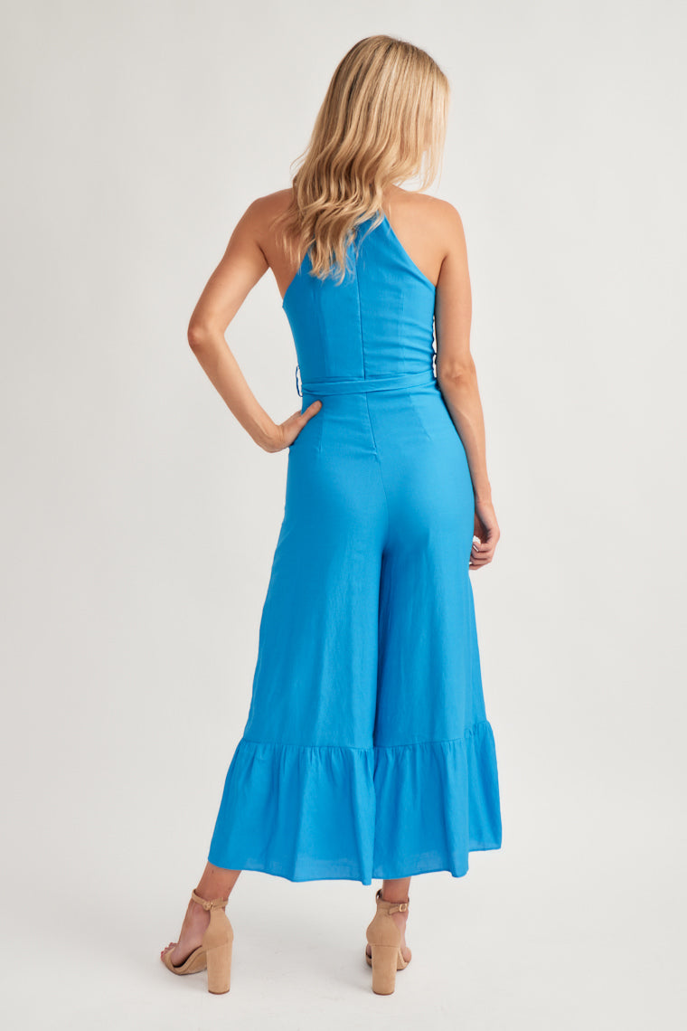 A gorgeous blue shade shapes this halter bodice with a fitted with a sash feature and a flowy, wide cut pant leg that flares at the hem.