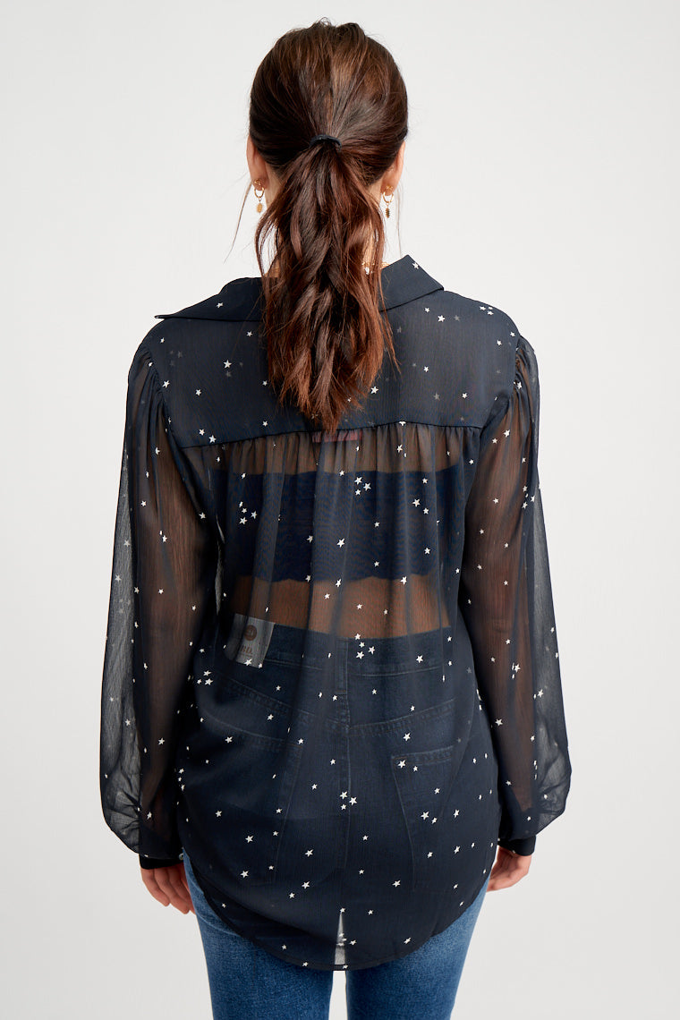 White tiny stars speckle the fabric of this deep navy blouse. Long button cuff sleeves attach to a collared neckline on a relaxed and sheer button-down bodice.