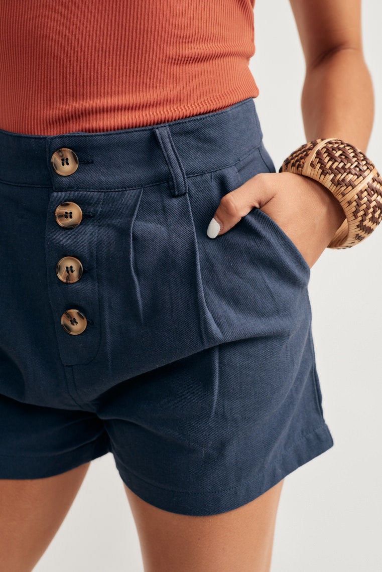 These lightweight navy shorts offer a banded waistline with an exposed button up fly, side seam pockets pleat, tailored fit and belt loops.