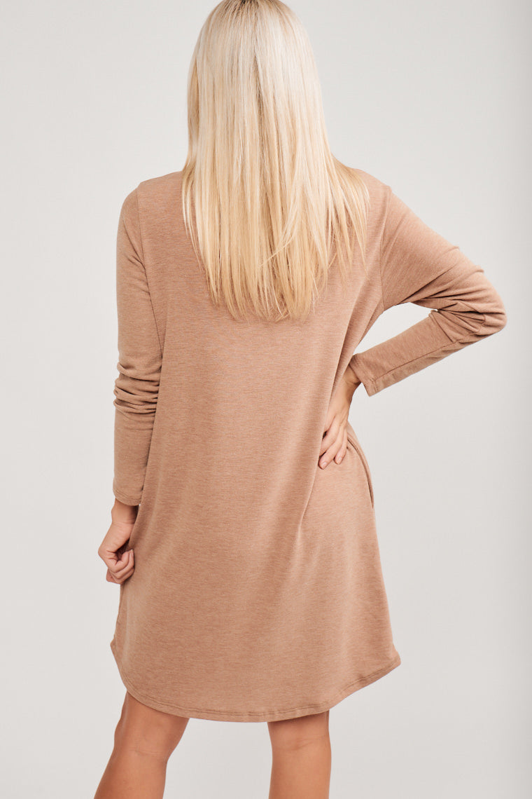Long fitted sleeves attach to a banded u-neckline and lead into a shift silhouette dress with pockets at the side. Style by pairing with thigh-high booties and a pendant necklace.