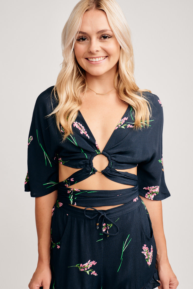 Green leaves attach to pink and white flowers on this top. Flowy mid-sleeved and has a deep v-neckline leading to circle ring with fabric pieces to wrap and tie at the midriff.