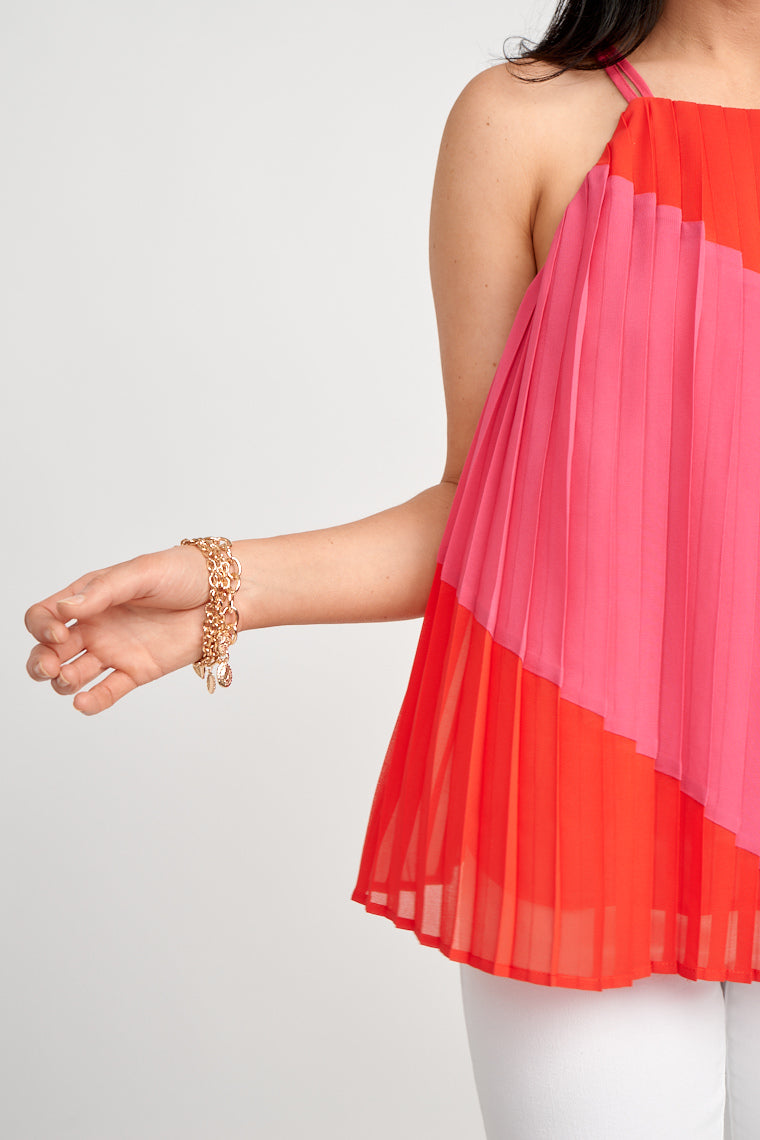 A pink color block stripe diagonally crosses the red fabric of this tank top. Double thin straps attach to a high u-neckline on a flowy and pleated shift bodice silhouette.