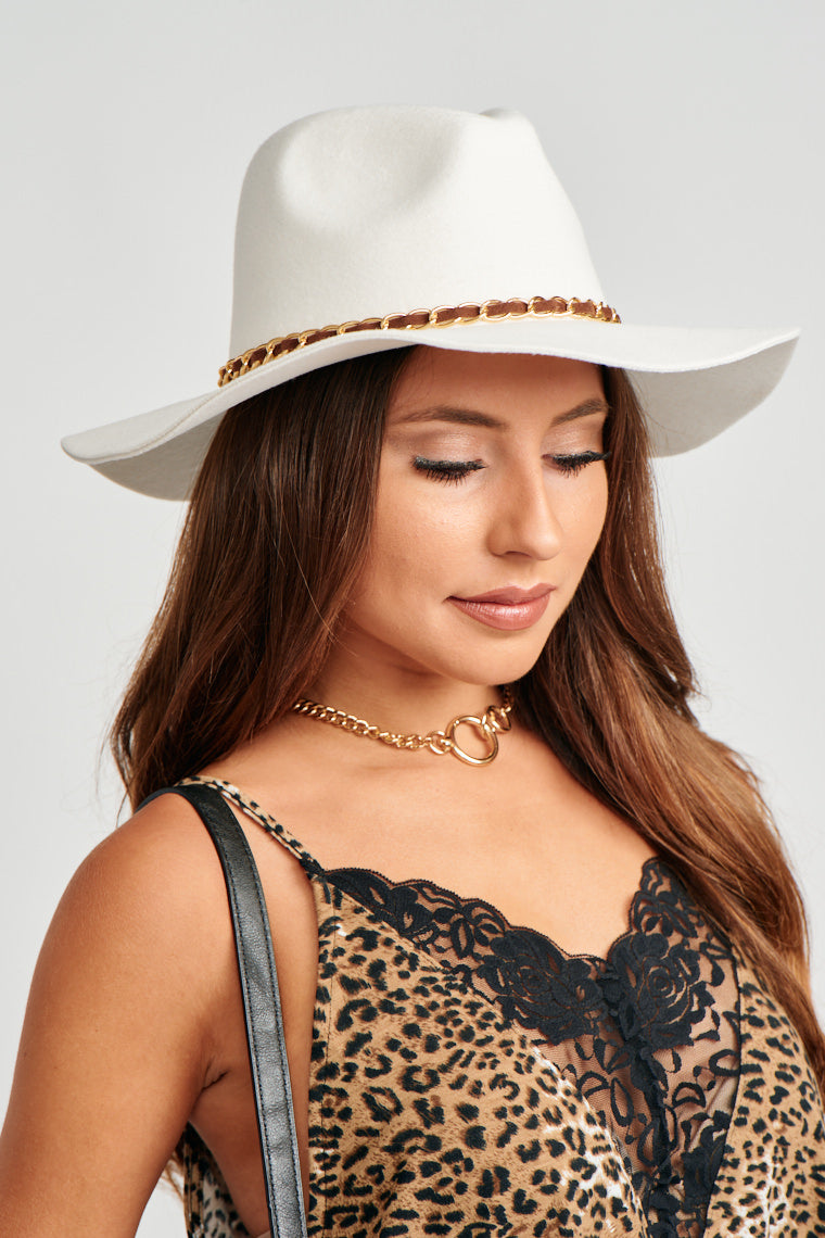 This medium brim woven Panama hat has a brown cord that goes through the middle of a gold chain and wraps around the crown of the hat.