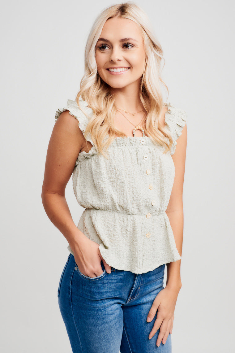 This crinkle fabric tank has ruffle straps that attach on a straight neckline with ruffle hem and relaxed button-down bodice that lead into a peplum waist silhouette.