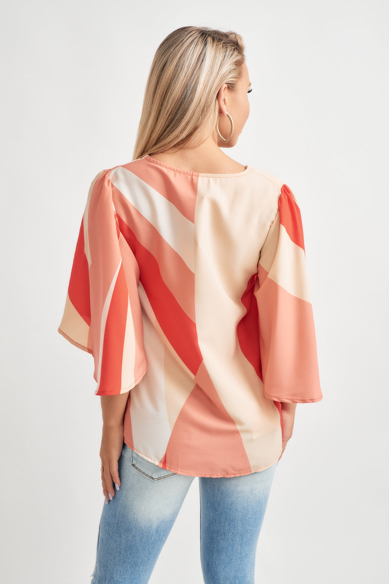 This lightweight pink, geometric color block blouse offers a v-neckline with short, flutter sleeves on a wide cut, relaxed bodice.
