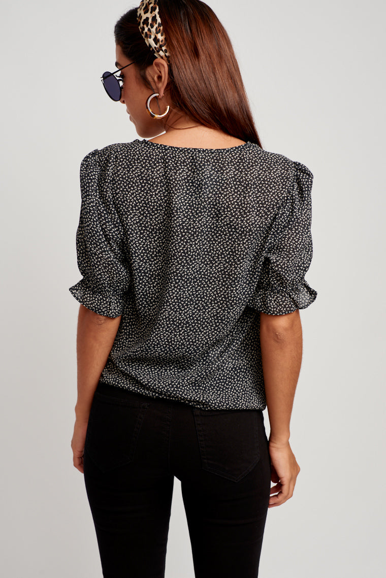 This printed blouse has gentle balloon sleeves with an elastic ruffle cuff that attach to a relaxed bodice with soft ruched detail down the center and a v-neckline.
