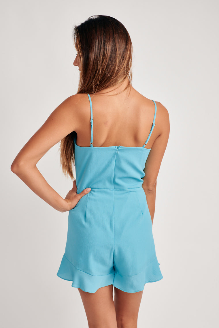 Bright blue, lightweight romper, with adjustable skinny straps support a straight neckline with a relaxed bodice and a side tie feature on the fitted waistline.