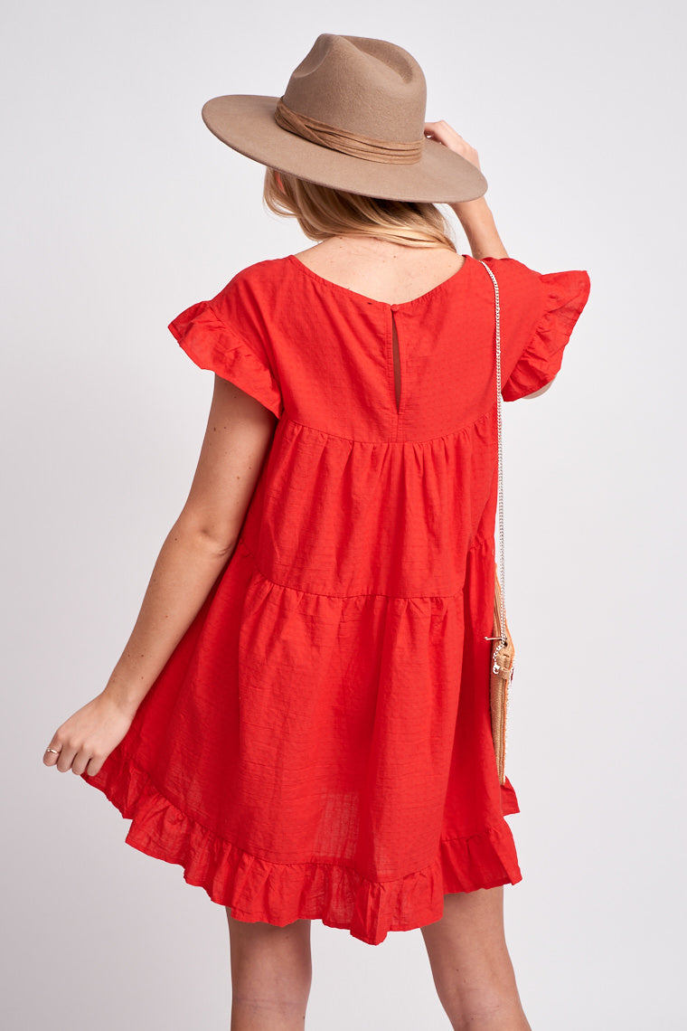 Short ruffle sleeves attach to a square neckline with a smock band across an oversized babydoll shift dress silhouette that is tiered and has a ruffle hem at the bottom.