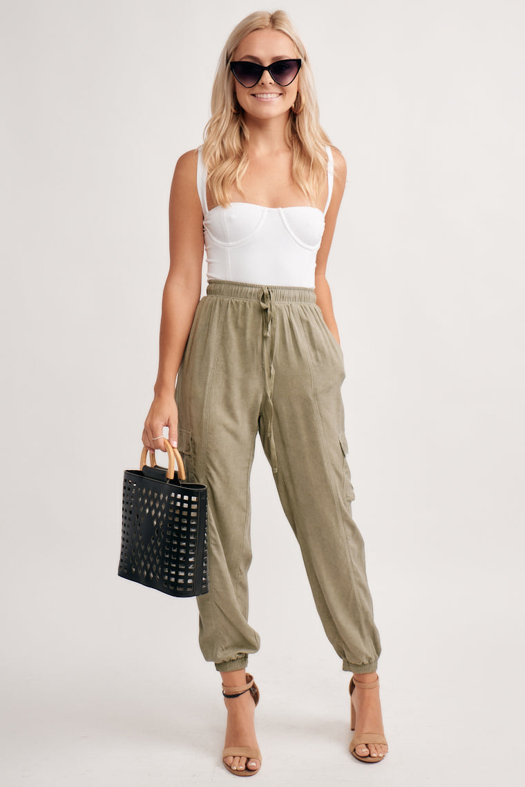 Roomy olive pants are lightweight with an elastic waistband and taper down the pantlegs to an elastic ankle cuff. These pants feature six total pockets.