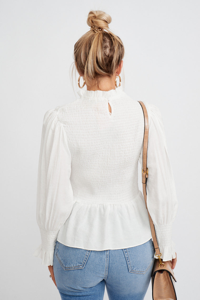 This lightweight top has long banded sleeves that attach to a high ruffle neckline on a smocked bodice and leads to a ruffle hem that flares out peplum-style.