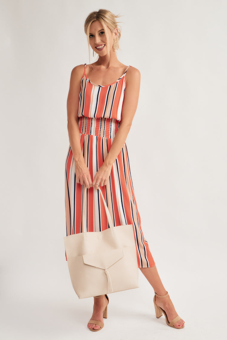 Coral, white, tan and navy stripes fall down the scoop neckline on the billowing bodices that transitions into a smocked waistline and straight midi skirt with a side slit.