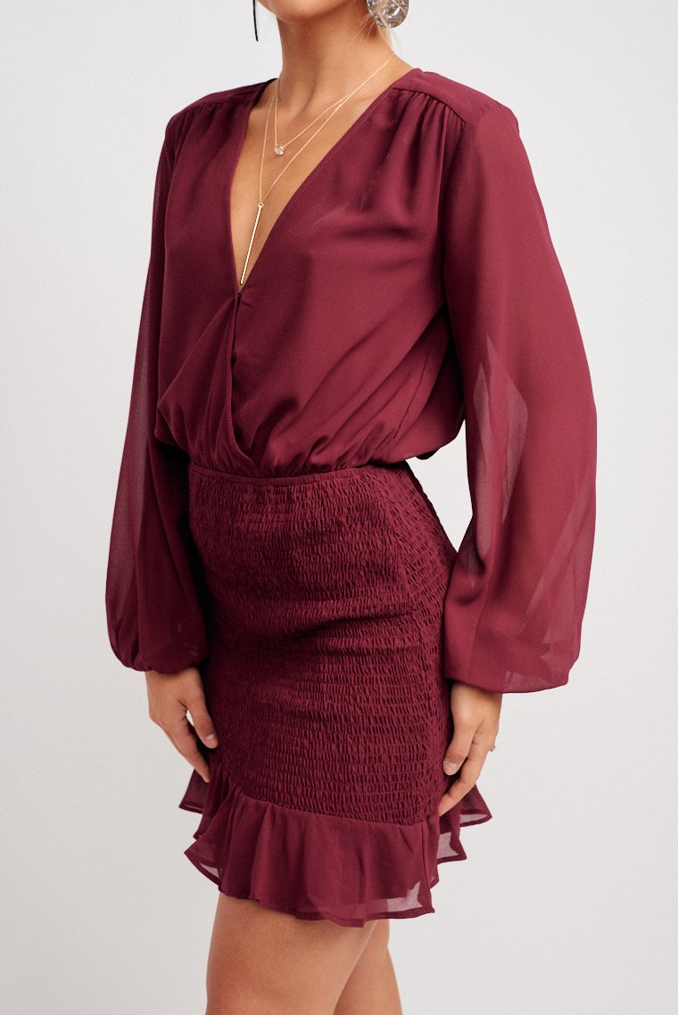 Long elastic cuff sleeves attach to a surplice neckline on a relaxed bodice silhouette and an elastic waistband and a smocked pencil skirt with a ruffle hem at the bottom.