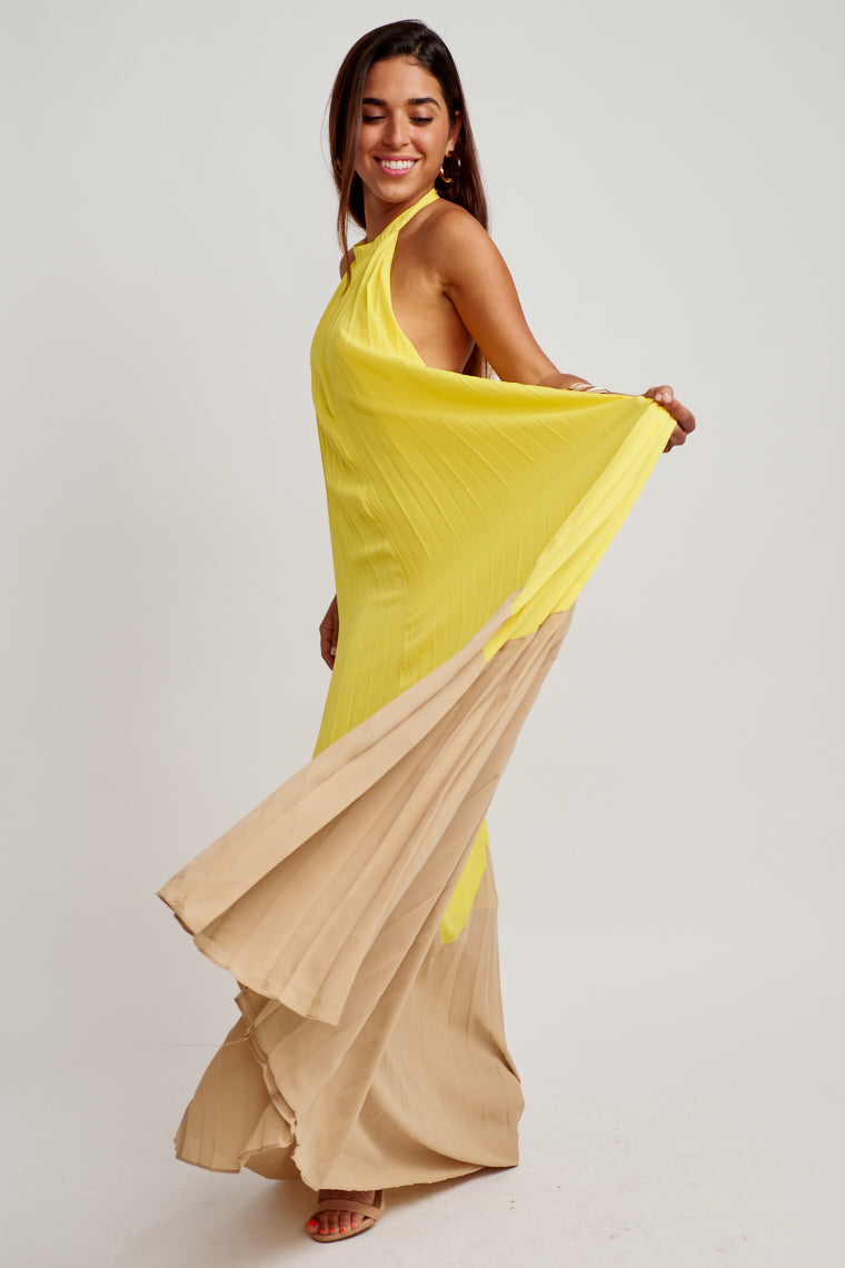 This banded halter neckline pleated maxi dress has yellow fabric that later transitions into a taupe fabric and an oversized silhouette. This dress features a button closure.