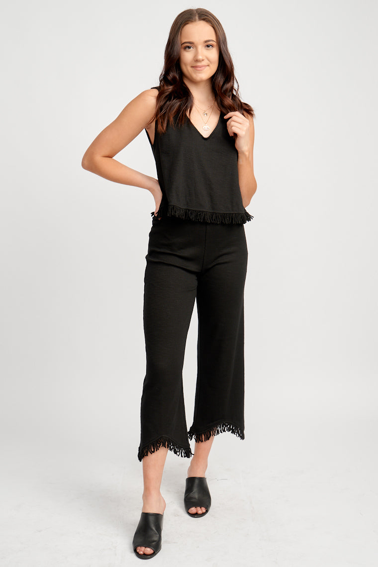 These stretchy pants have an elastic waistband that leads to a relaxed and loose fit pant silhouette. It crops at the bottom half and has fringe at the bottom of the legs.