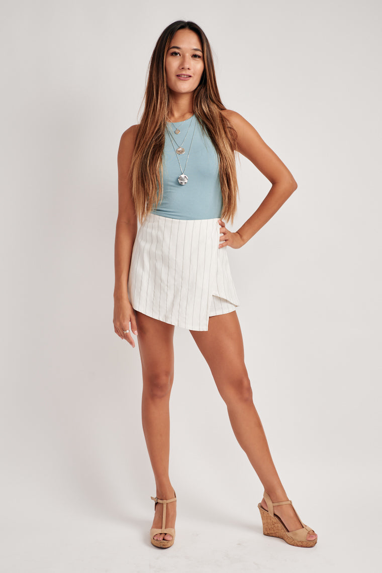 White with black pinstripes forms this adorable relaxed shorts with an asymmetric skirt over top the front gives a mid-rise fit.