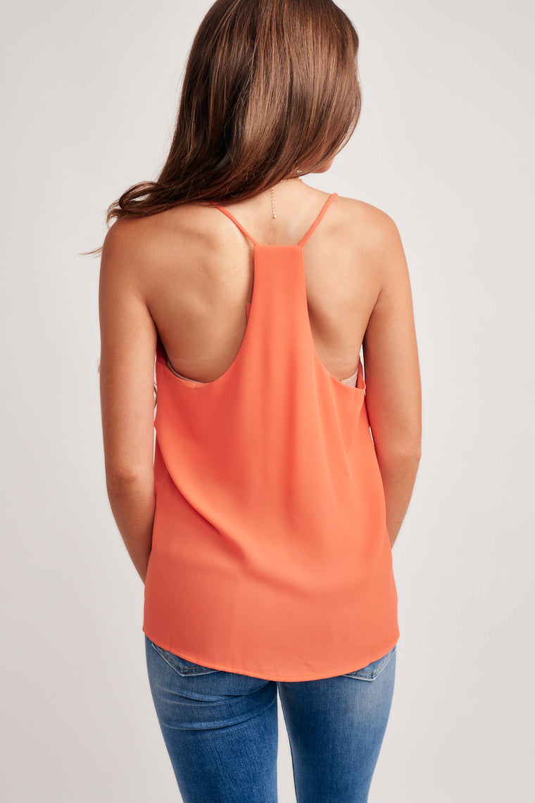 This vibrant orange tank top offers a v-neckline with thin straps that goes into a flowy bodice and a racerback. Pair your summer look by styling with jeans.