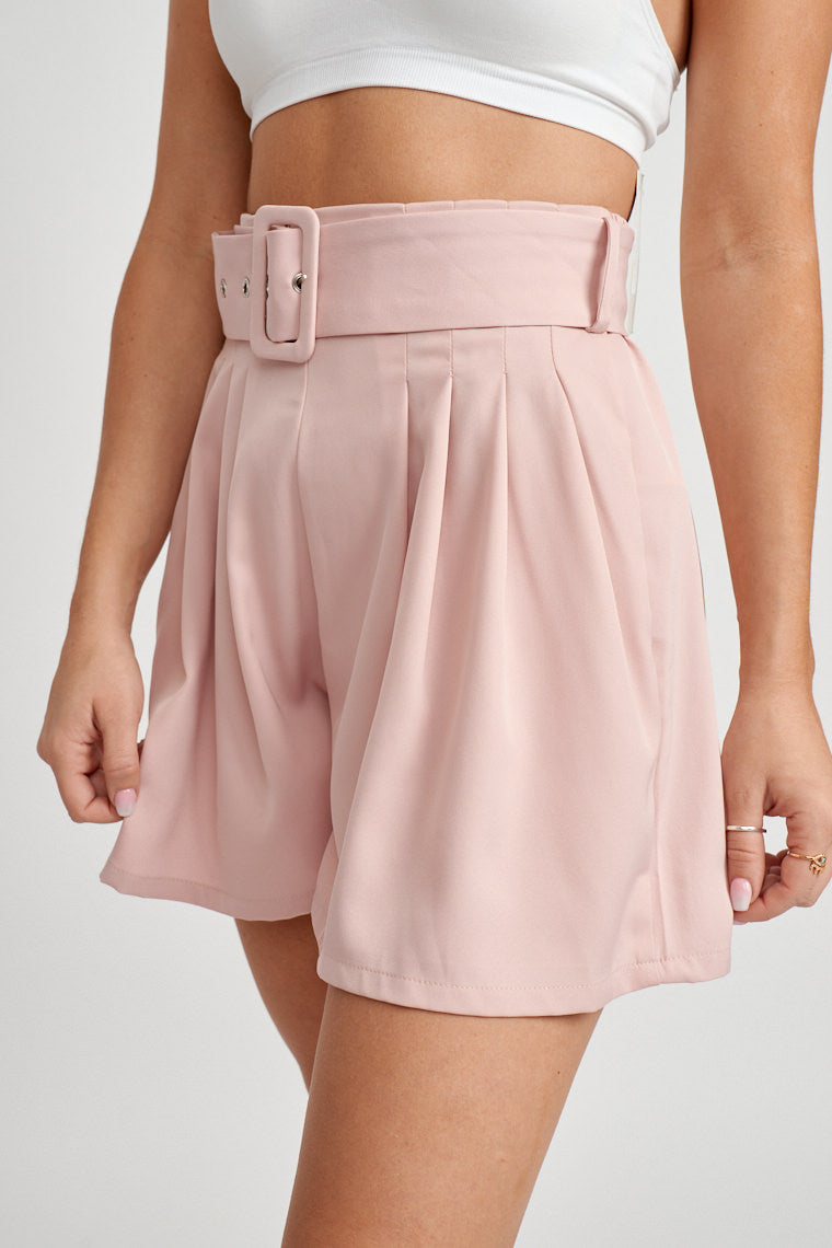 These belted shorts have a relaxed fit with inverted pleats and a rectangle buckle fabric belt atop the waistband. Style it with bodysuits, tees, or crop tops.