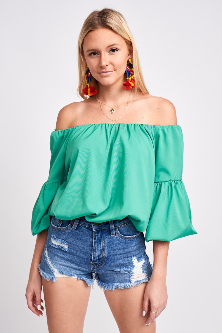 Mid-length puffed bishop sleeves attach to an off-the-shoulder and straight neckline on an oversized and relaxed bodice silhouette with an elastic waistband.