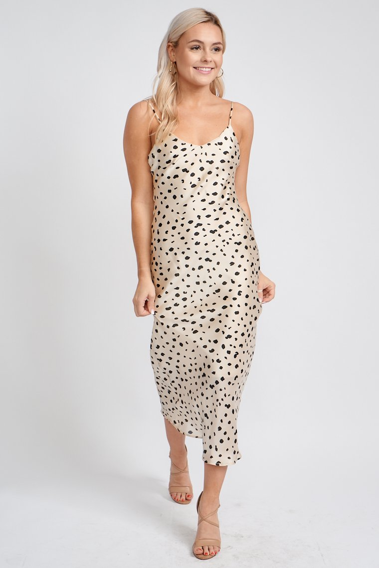 Black dots speckle across the fabric while skinny adjustable straps attach to a v-neckline and flow into a darted bodice and relaxed fit skirt that meets the top of the ankle.