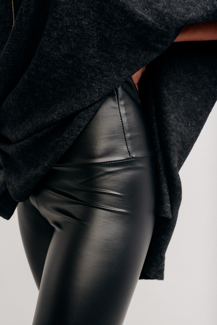 These high-rise leggings have a shiny fabric and a banded waistband that goes into a fitted hip silhouette and into leg hugging pant legs.