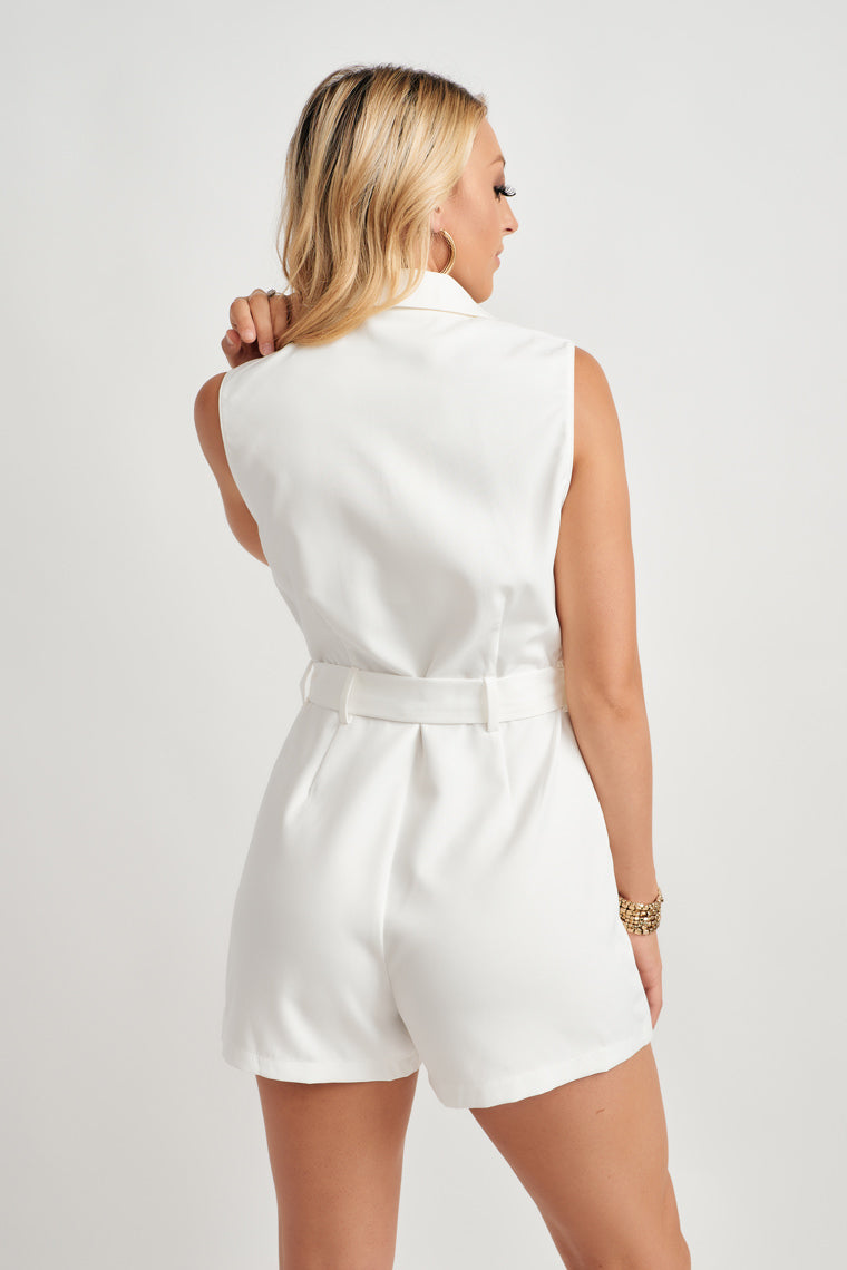 This sleeveless, blazer-inspired romper features a notched collar v-neckline, with a button-down silhouette, two front pockets, and a tying sash waistline.