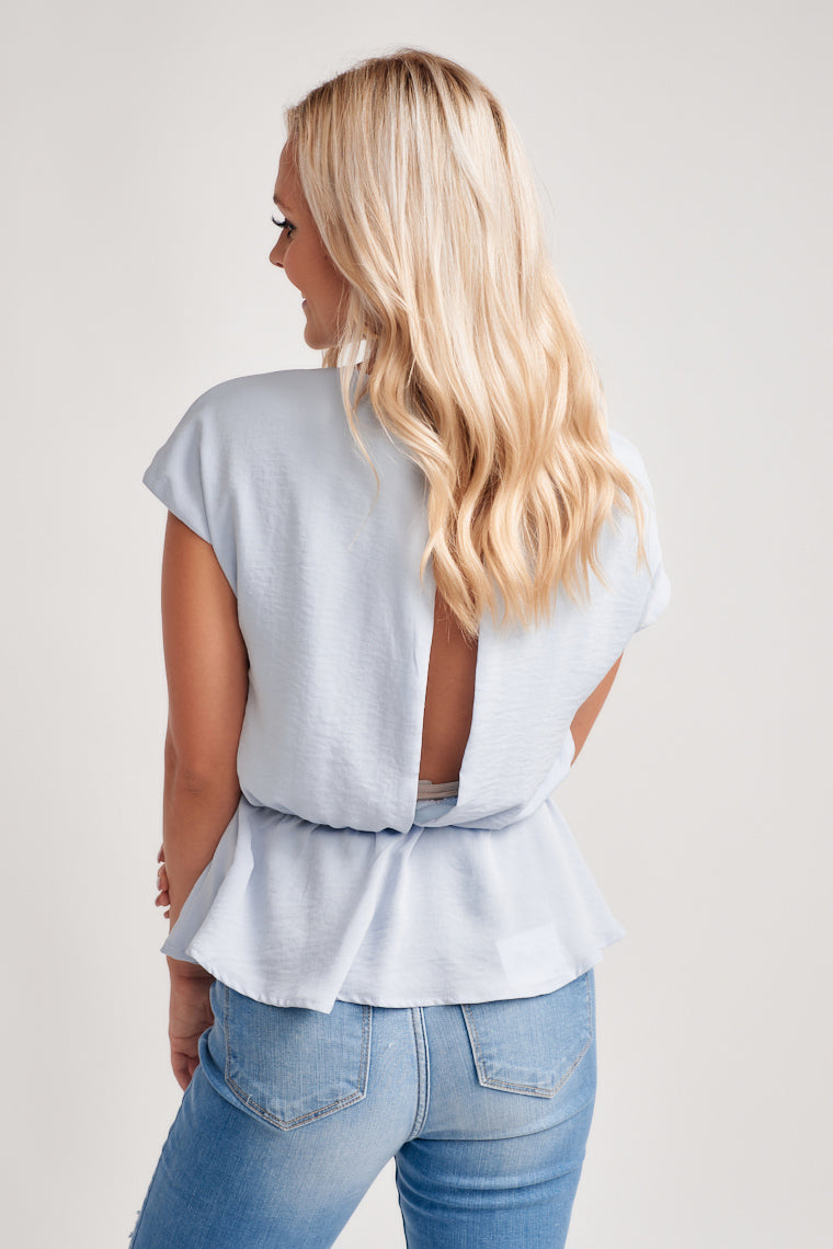The modest v-neckline carries into a relaxed bodice with a tie front atop the cinched waistline. The peplum hem and sliver-slit down the back with a top button.