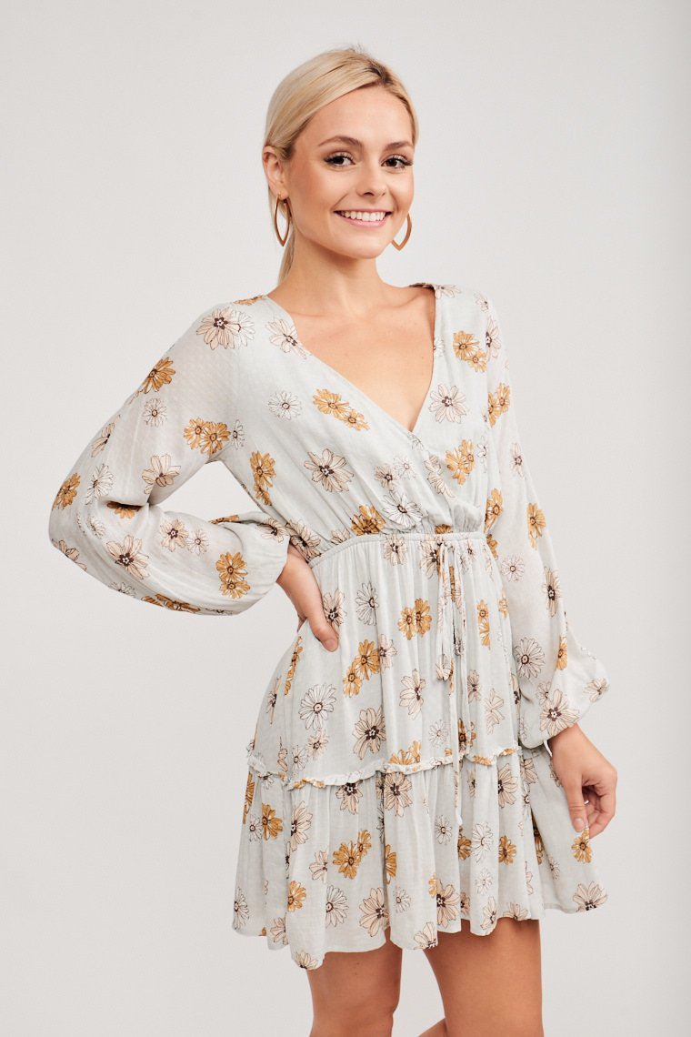 Long sleeves attach to a surplice neckline with a relaxed bodice that meets an elastic waistband with faux drawstring and flows into a tiered skirt with a ruffle hemline.