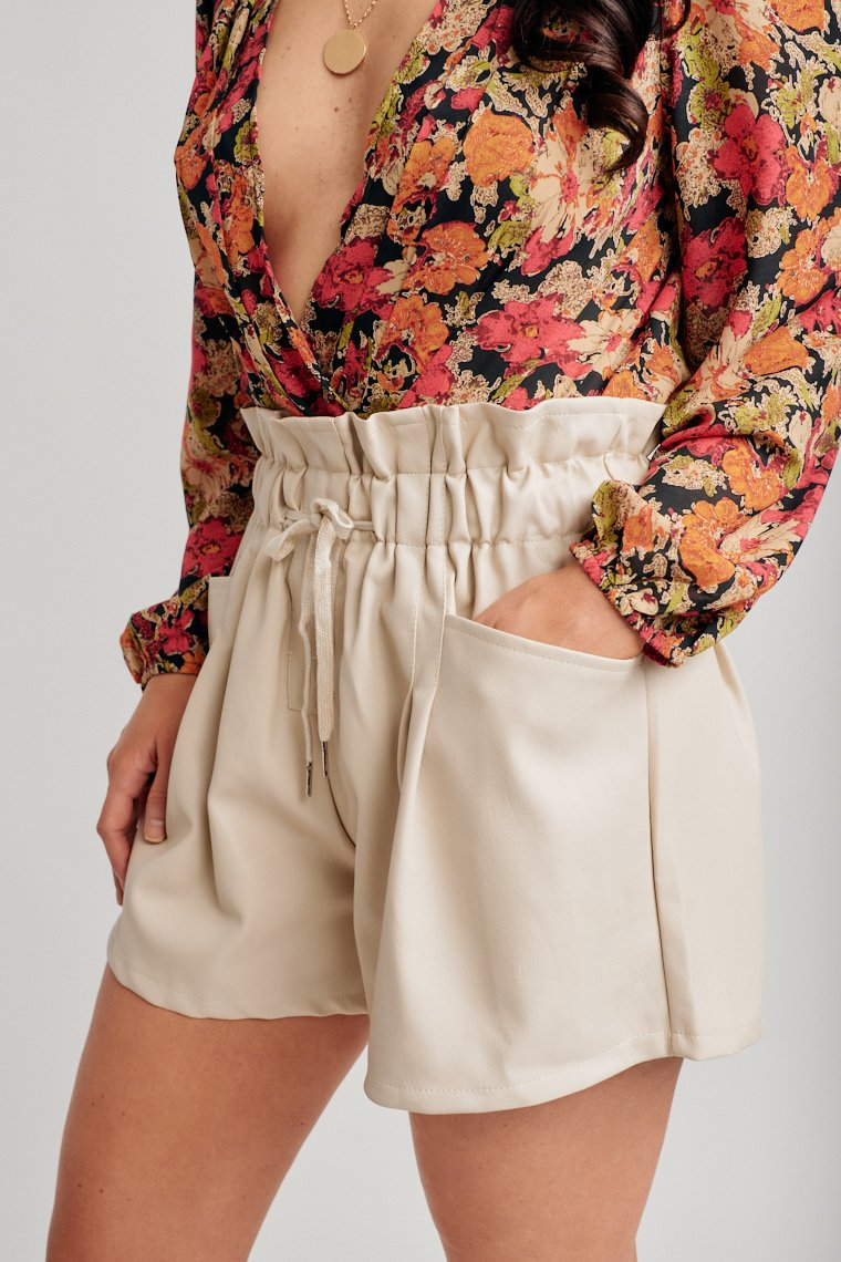 These shorts have a paper bag waistband with an elastic and drawstring tie that leads to pockets at the side and goes into loose-fitting relaxed shorts.