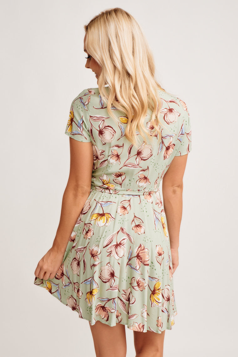 This sage dress is decorated in flowers outlined in black, short sleeves lead into a surplice neckline, ties on the side, and waistline flows into a high-low skirt.