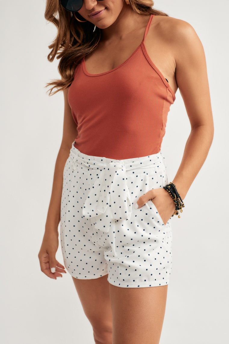 Cute black polka dots decorate these white summer shorts offering a mid-rise, tailored fit with side seam pockets and belt, tying sash around the waistline.