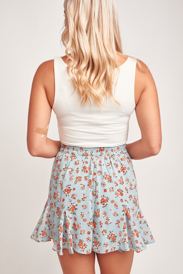 Orange and white floral prints are speckled throughout these relaxed godet detailed shorts. The shorts have a stretchy elastic waistband. Pair with a white tank!