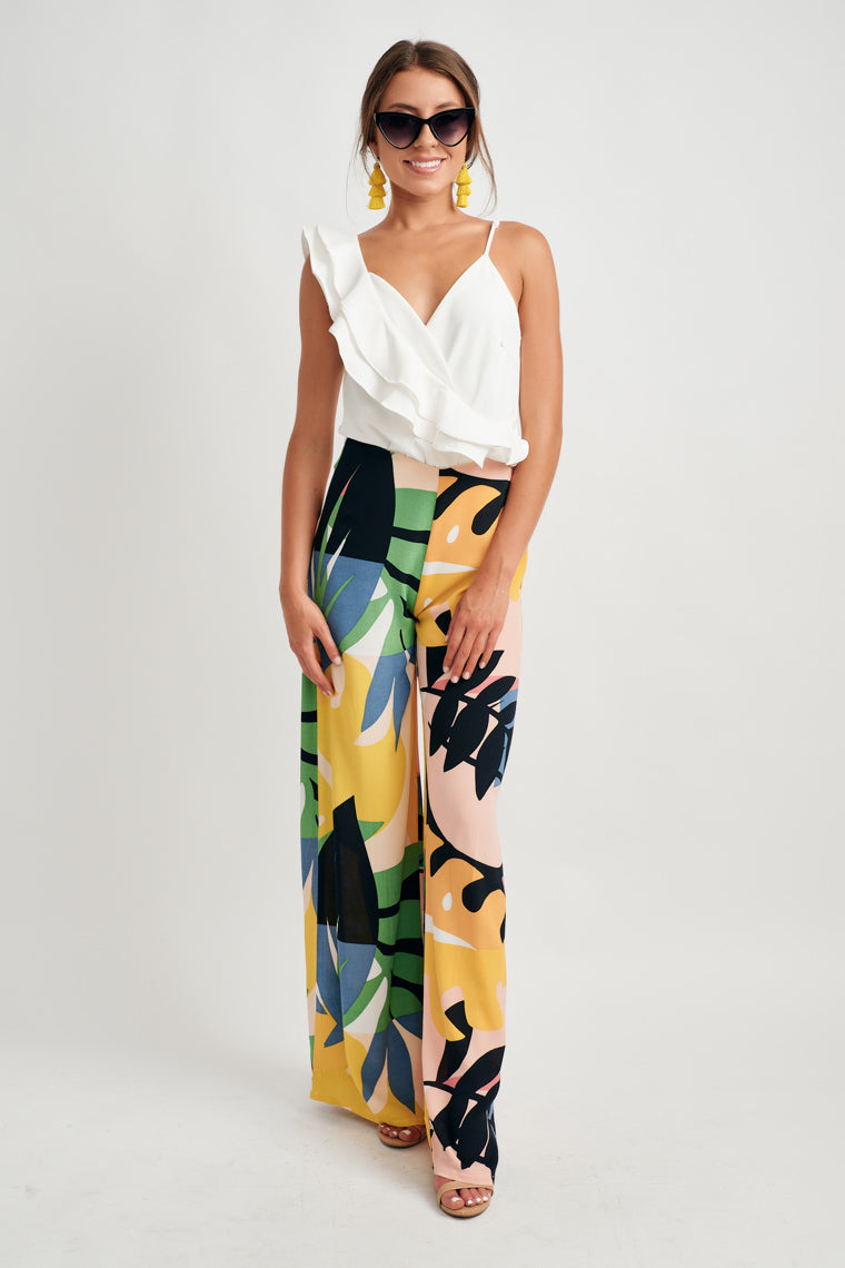 Tropical leaves in multiple colors lay overtop one another to form this unique summer print that decorates this high-rise, fitted waistline that flowy into a long, wide pant leg.