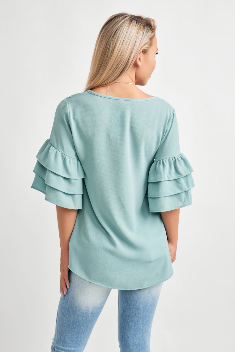 This lightweight baby blue blouse offers a v-neckline with half, ruffled sleeves on a wide cut, relaxed bodice.