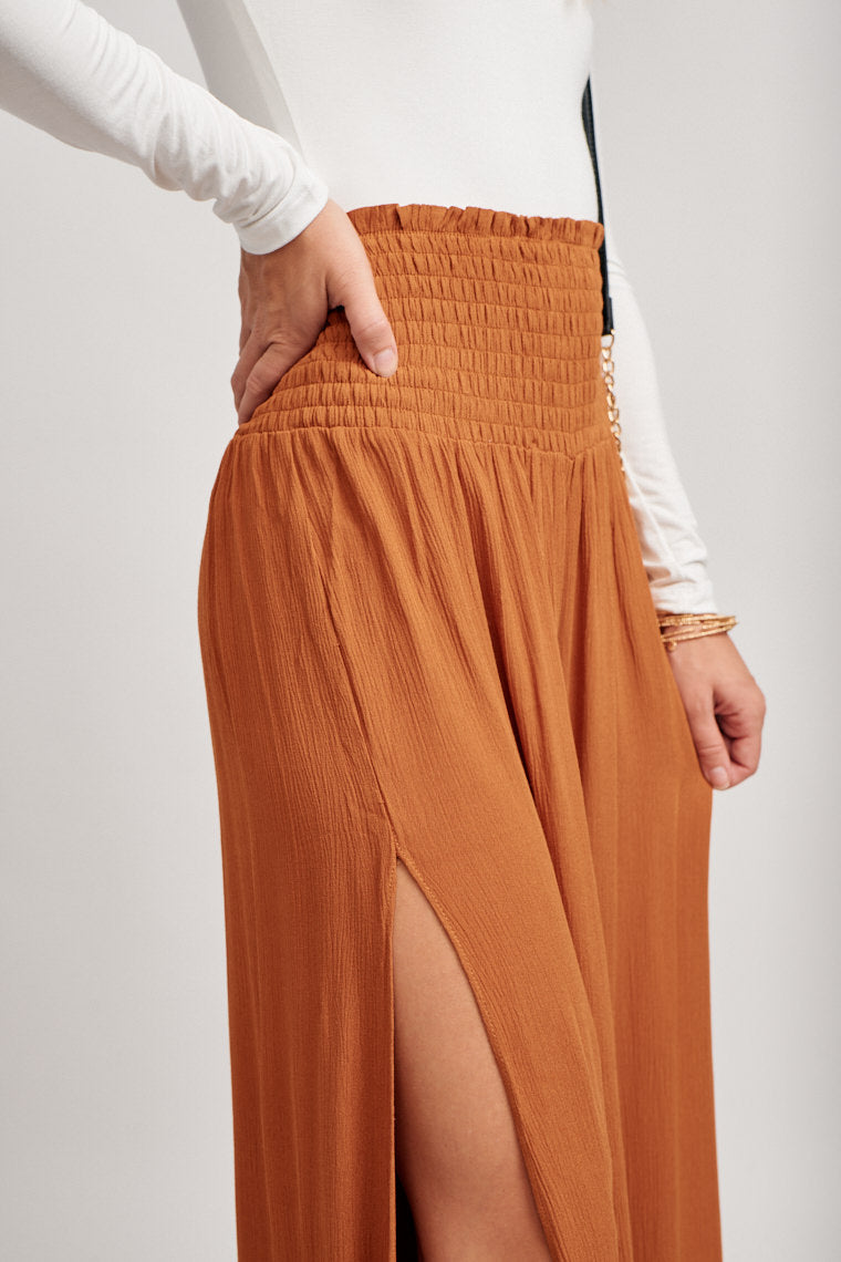 These pants have a high-rise smock waistband that leads to flowy pant legs with a side slit. Pair with a sweater, black sandals, and a black brim hat.