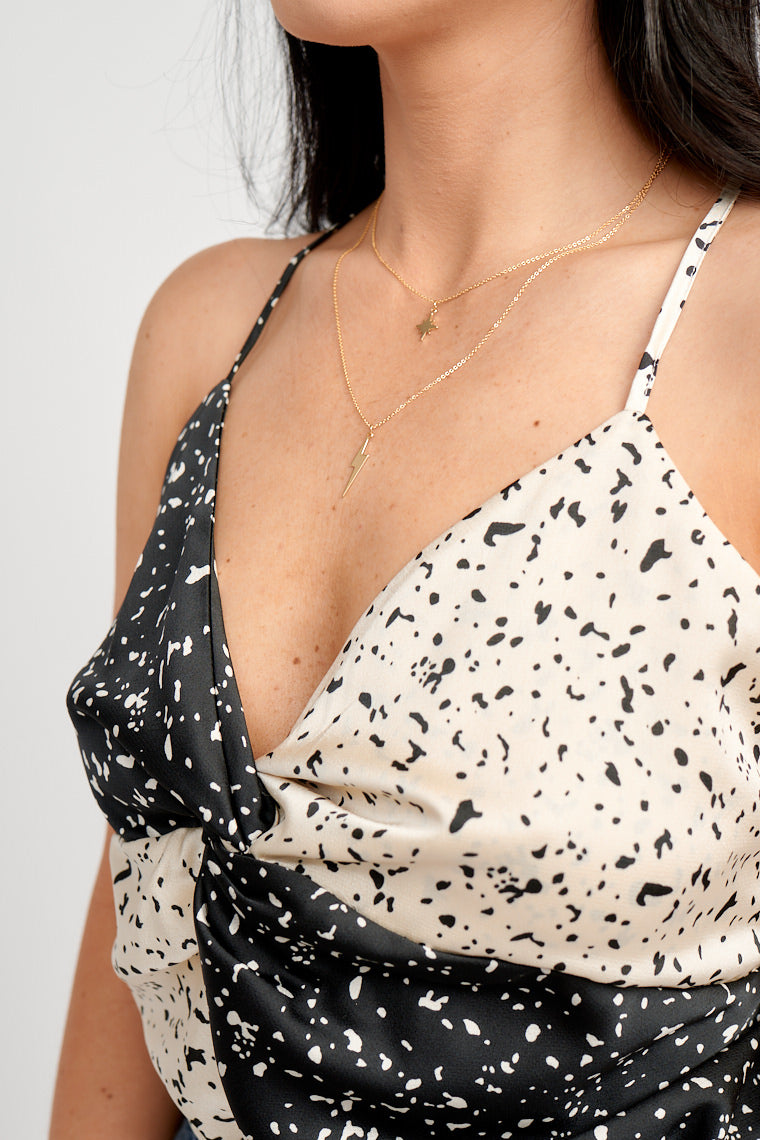 Black and white color block with contrasting speckles, thin adjustable straps attach to a v-neckline on a twisted bodice detail meeting an elastic waistband and cheeky briefs.
